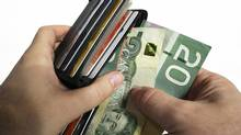 Paying Cash with Canadian Currency- The action of pulling canadian money out of a wallet. Twenty dollar bills. (Denis Pepin)