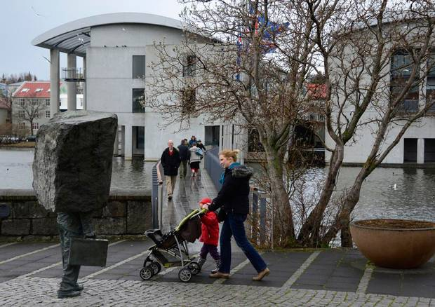 A woman pushes a stroller as she passes the City Hall polling station in Reykjavík, Iceland.