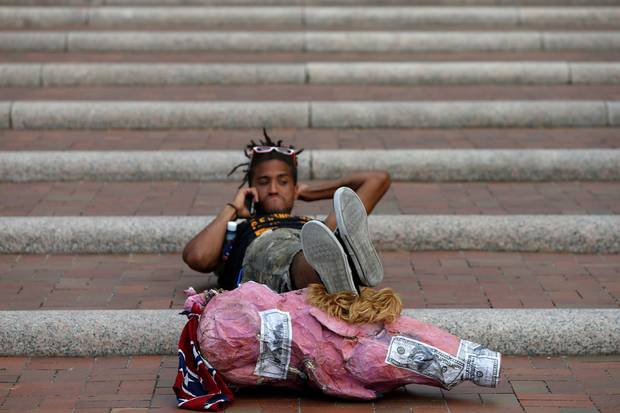 A protester in Cleveland reclines on a set of stairs using a Donald Trump pig puppet as a footrest.