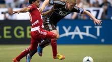 FC Dallas' David Ferreira, left, of Colombia, and Vancouver Whitecaps' Barry Robson, of Scotland, battle for the ball during the first half of an MLS game in Vancouver, B.C., on Wednesday August 15, 2012. (DARRYL DYCK/THE CANADIAN PRESS)