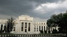 Storm clouds gather over the U.S. Federal Reserve Building before an evening thunderstorm in Washington in this June 9, 2006 file photo. (Reuters)