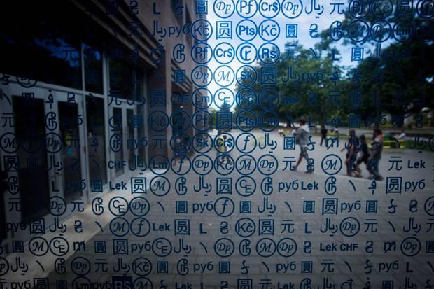 International currency symbols adorn a window of UBC's Sauder building.