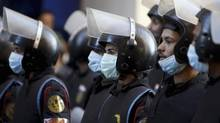 Riot police look on during clashes in Simon Bolivar Square, which leads to Tahrir Square, in Cairo, Jan. 30, 2013. (MOHAMED ABD EL GHANY/REUTERS)