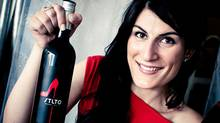 Sarah Liberatore, founder of STLTO, holds up a bottle of her red wine (CIBELE ZAPPAROLI/COURTESY OF STLTO)