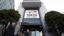 Pedestrians walk past Japan Exchange Group Inc.'s Tokyo Stock Exchange (TSE) on the first trading day of the year in Tokyo, Japan, on Friday, Jan. 4, 2013. (Kiyoshi Ota/Bloomberg)