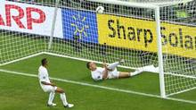 England's Ashley Cole (L) watches as England's John Terry (R) clears the ball from the goal mouth during their Group D Euro 2012 soccer match at the Donbass Arena in Donetsk, June 19, 2012. (FELIX ORDONEZ/REUTERS)