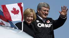 Conservative Leader Stephen Harper waves as he disembarks his campaign plane with his wife, Laureen, in Comox, B.C. on April 23, 2011. (CHRIS WATTIE/REUTERS)