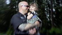 Ryan Knighton holds his daughter Tess Rawa-Knighton. (CP)