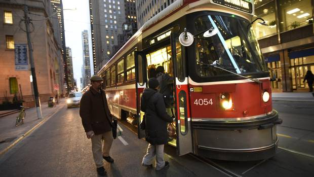 Commuters board an eastbound King Street streetcar at Yonge Street in Toronto.