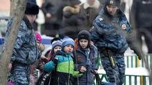 Police officers evacuate children from a Moscow school on Feb. 3, 2014. (Alexander ZAemlianichenko/Associated Press)