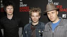 "Members of the Ontario, Canada-based band Sum 41 Cone McCaslin, left, Deryck Whibley, center, and Steve Jocz, right, pose backstage during MTV's ""Total Request Live"" at the MTV Times Square Studios Thursday, May 31, 2007 in New York (Jason DeCrow/AP)"