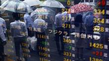 Passersby holding umbrellas are reflected on an electric stock quotation board outside a brokerage in Tokyo June 21, 2013. (Issei Kato/REUTERS)