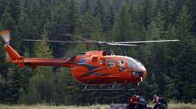 Members of a search and rescue crew return to Kaslo, B.C., Sunday, July 15, 2012, from a landslide that buried three homes and has left four people unaccounted for in Johnsons Landing, B.C. (Jeff McIntosh/THE CANADIAN PRESS)