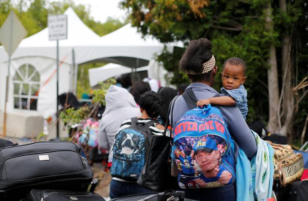 A line of asylum seekers who identified themselves as being from Haiti wait to enter into Canada from Roxham Road in Champlain, New York.