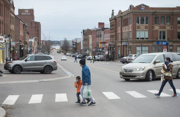 Pedestrians walk across Queen Street in downtown Charlottetown, PEI.