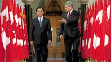Canadian Prime Minister Stephen Harper gestures to Chinese President Hu Jintao as they walk through the Hall of Honour on Parliament Hill in Ottawa on June 24, 2010. (Adrian Wyld/The Canadian Press)