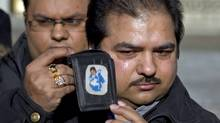 Dinesh Kumar shows a picture of his son Gaurov outside court in Toronto on Jan 20, 2011, after being acquitted of causing the boy's death in 1992. (Chris Young/Chris Young/The Canadian Press)