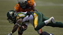 BC Lions corner back Cord Parks tackles Edmonton Eskimos running back Hugh Charles during the second half of their CFL football game in Vancouver on July 20, 2013. (© Andy Clark / Reuters/REUTERS)
