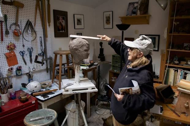 Frances Gage demonstrates her clay-application technique on a bust of Owen Hellum, in her studio in Cobourg, ON in 2009.