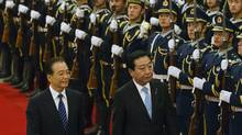 Japanese Prime Minister Yoshihiko Noda, right, is escorted by Chinese Premier Wen Jiabao inspect a guard of honor during a welcoming ceremony at Great Hall of the People in Beijing, China, Sunday, Dec. 25, 2011. Noda arrived in Beijing on Sunday for talks focused on North Korea and promoting stability in the closed country after the death of Kim Jong Il. (Andy WongAP/Andy WongAP)