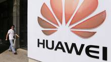 A man walks past a Huawei company logo outside the entrance of a Huawei office in Wuhan, Hubei province in this October 9, 2012 file photo. (Reuters)