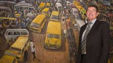 Peter Kieran, president and CEO of CPCS, is shown at the company's offices in Abuja, Nigeria. Behind him is a painting showing the notoriously chaotic traffic in Lagos. (Erin Conway-Smith for The Globe and Mail/Erin Conway-Smith for The Globe and Mail)
