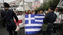 Greek Red Cross workers, who have not been paid for five months, face police as they demonstrate in front of the Greek Parliament the Greek Parliament on October 11, 2011. (LOUISA GOULIAMAKI/AFP/Getty Images)
