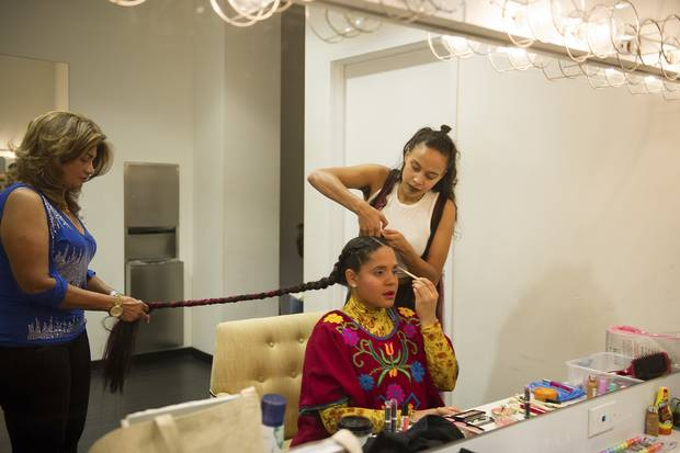 Lido Pimienta has her hair done by her mother, Rosario Paz, left, and friend and artist Ruth Titus, right, before her set at Venus Fest.