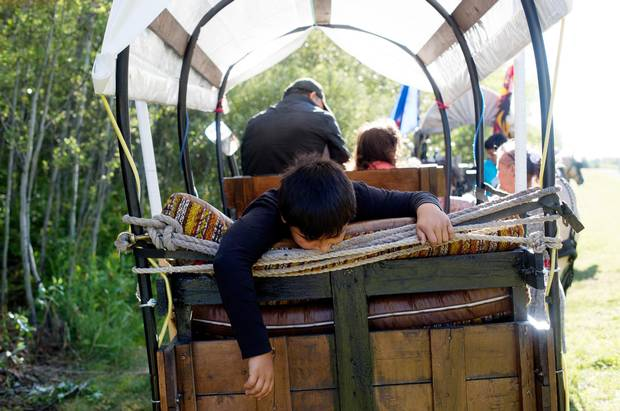 Nolan Jong waits in the back of a wagon for the Driftpile First Nation caravan to make the final journey to Lac Ste Anne, Alberta on Sunday, July 19, 2015. Members of Driftpile First Nation traditionally made the trip by horse and people have reestablished the practice for the last 15 years.