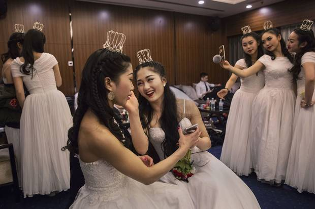 Debutantes from a local academy laugh as they get ready to take part in the Vienna Ball at Beijing's Kempinski Hotel on March 19, 2016. Social mobility and economic status are largely shaped by hukou.