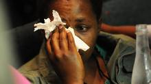A woman cries after watching graphic video footage of South African police shooting striking miners at the Lonmin mine in Marikana, during an official inquest in Rustenburg, South Africa, Oct. 23, 2012. (AP)