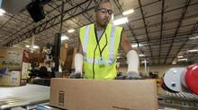 A worker sends a package on its way at Amazon.com's warehouse in Goodyear, Ariz. (Ross Franklin/Ross Franklin/AP)