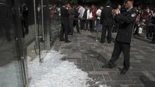 In this photo taken on Saturday May 7, 2011, a Chinese policeman takes photos of the broken glass door in the aftermath of a scuffle at Apple's Sanlitun retail store in Beijing during the release of the iPad2. (Associated Press)