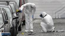 Forensic experts examine the site of a shooting at the Jewish museum in Brussels on May 24. (Yves Logghe/AP)