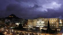 A storm illuminates the sky over the Greek parliament in Athens Jan. 24, 2013. (YORGOS KARAHALIS/REUTERS)