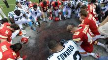 Kansas City Chiefs and Carolina Panthers players form a prayer circle after the Chiefs' win in a NFL football game in Kansas City (DAVE KAUP/REUTERS)
