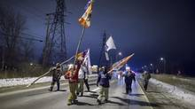 Protesters march down Highway 40 after abandoning their blockade of the CN tracks in Sarnia, Ont., on Wednesday. (Geoff Robins/THE CANADIAN PRESS)