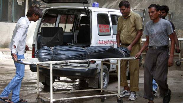 Hospital staff move the body of Awanish Kumar Dev, human resources manager at the Maruti Suzuki plant in Manesar, India, on Thursday. He was killed during a riot at the factory on Wednesday. The plant was closed on Thursday and the company's share price suffered its biggest loss in almost two years. (STRINGER/INDIA/REUTERS)