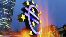 Activists of the Occupy Frankfurt movement have set up a fireplace near the Euro sculpture in front of the European Central Bank in Frankfurt, Germany, Thursday, Nov.3, 2011. The ECB announced to lower their key interest rate to 1.25 percent. (AP Photo/Michael Probst) (Michael Probst/AP)