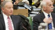 Stacks of cost-estimate documents sit on a desk behind Justice Minister Rob Nicholson and Public Safety Minister Vic Toews as they testify a Commons committee on March 16, 2011. (Sean Kilpatrick/THE CANADIAN PRESS)