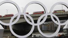 A barge with the Olympic rings floats below London Bridge as a line of double decker buses cross it during a promotional event on the Thames in London, February 28, 2012. Picture taken February 28, 2012. REUTERS (ANDREW WINNING)