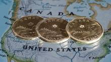 Canadian dollar coins are displayed on a map of North America. (Paul Chiasson/The Canadian Press)