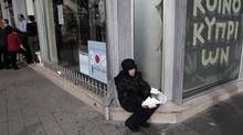 A woman holds a bank cheque outside a branch of the Bank of Cyprus in Nicosia. (Petros Giannakouris/AP)