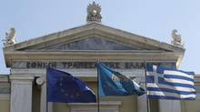 Flags from right, Greek, National Bank of Greece and the European Union flags wave outside the headquarters of the National Bank of Greece in Athens. (Petros Giannakouris/Petros Giannakouris/AP)