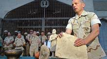 US Colonel Matthew Bogdanos, lead investigator in finding looted treasures taken from the Baghdad Archeological Museum, directs a presentation to the press in Baghdad, 16 May 2003. Investigators have recovered 951 artifacts and determined many items had been stored for their security in pre-war hidding sites. One of the oldest known bronze relief bowls, an Assiryan pottery jar from the sixth millenium B.C., one of the earliest known Sumerian free-standing statue and a carved rock from the Babilonic period were pesented to the press. (BEHROUZ MEHRI/AFP)