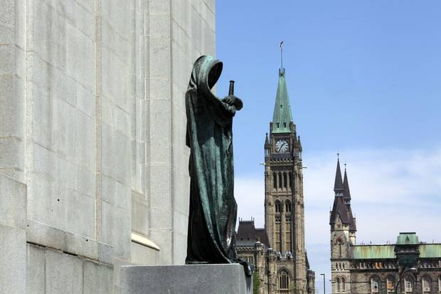 Ottawa's Parliament buildings loom behind the statue of Ivstitia (Justice) on the front steps of the Supreme Court of Canada.
