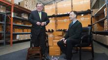 Finance Minister Jim Flaherty tries on a pair of shoes with Andrew Violi, president of Mello Walk Shoes, at a pre-budget press event in Toronto. (AARON VINCENT ELKAIM/THE CANADIAN PRESS)