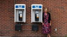 Penny Leclair stands next to two pay phones in Ottawa. (Dave Chan for The Globe and Mail)