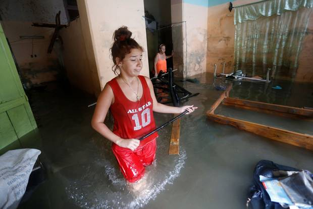 Havana, Sept. 10: A woman reacts while wading through her flooded home after Irma's passing.