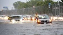 Flooded cars are stranded during a storm in Toronto July 8, 2013. TD Bank Group is expecting a third-quarter net loss of between $240-million and $290-million after tax due to flooding in Alberta and Toronto this year. (FRANK GUNN/THE CANADIAN PRESS)